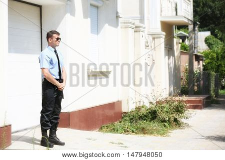 Male security guard beside garage