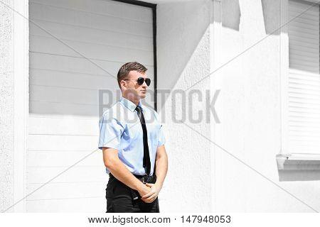 Male security guard beside garage