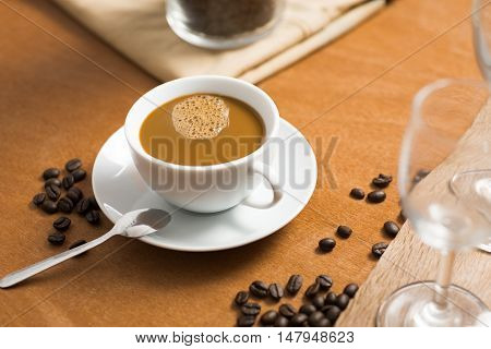 coffee cup with bean on wood table in coffee shop