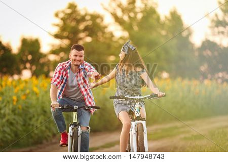 Young couple on bicycles in field