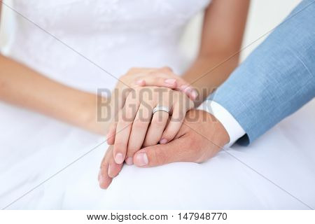 Bride and groom holding hands together indoor