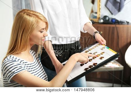 Beautiful young woman choosing color hair from palette at hairdressing salon