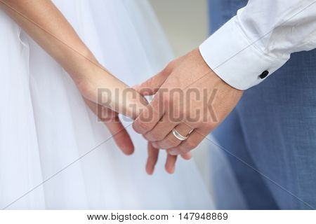 Bride and groom holding hands together outdoor