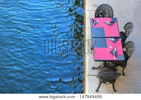 Waterfront pizza restaurant table with pink place mats next to the blue water