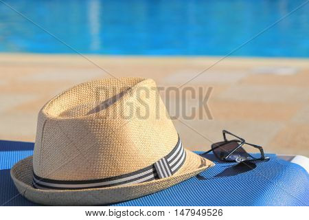 Straw Hat And Sunglasses On A Poolside Sunlounger In Early Morning Sunshine