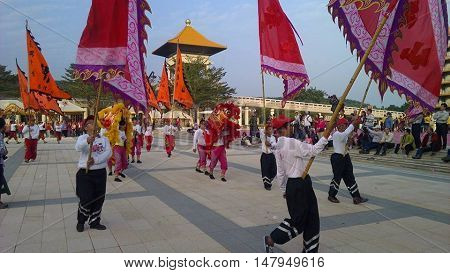 Flags, dancing, and people in parade at Buddhist temple in Taiwan.