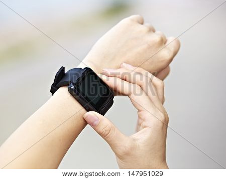 hands of a young female operating a black smart watch