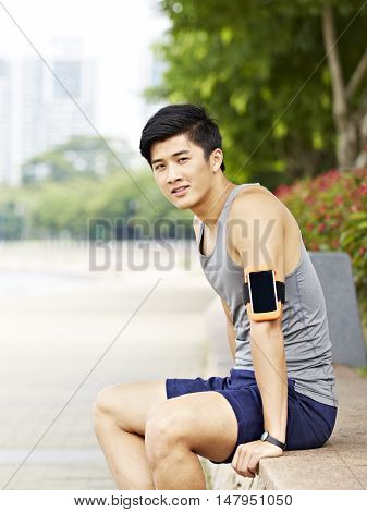 young handsome asian jogger wearing fitness tracker taking a break in a city park looking at camera smiling.