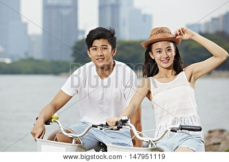 young asian couple riding bike in urban park looking at camera smiling