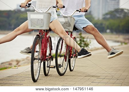 young man and woman having fun riding bikes in the park