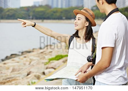 young asian couple tourists trying to locate a scenery spot using a map