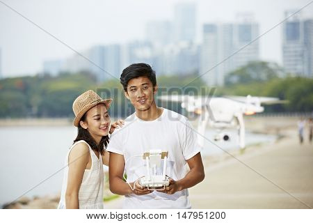 young asian couple operating a drone in a city park