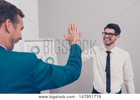 Portrait of happy young businessman giving high five to his colleague