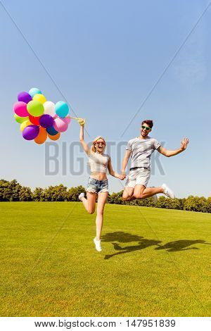Happy Man And Woman Holding Balloons And Jumping In The Park