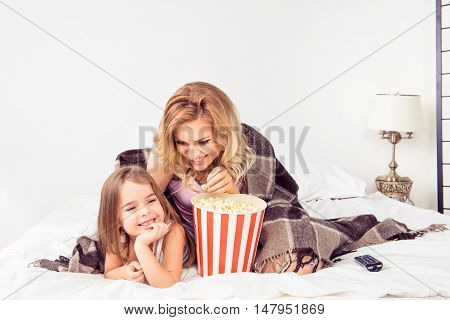 Portrait Of Happy Mother And Her Daughter Watching Cartoons With Popcorn In Bed