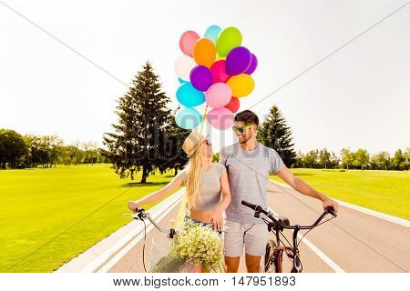 Portrait Of Happy Couple In Love Walking With Bicycles And Balloons