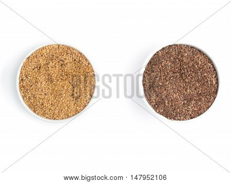 Gold and brown linseed into a bowl in white background