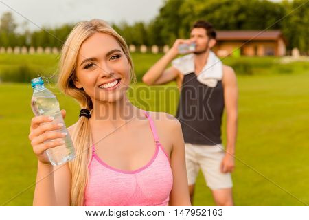 Portrait Of Pretty Smiling Woman Holding Bottle Of Watter. Her Boyfriend Drinking Behind Her