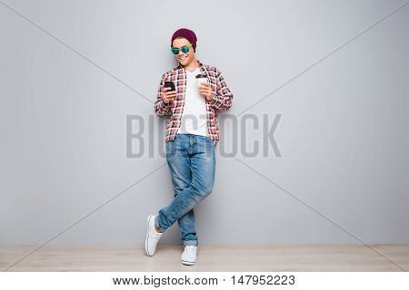 Full Portrait Of Hipster Man Holding Cup Of Coffee And Typing Sms