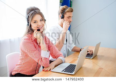 Portrait Of Man And Woman In Headphones Working In Call Center
