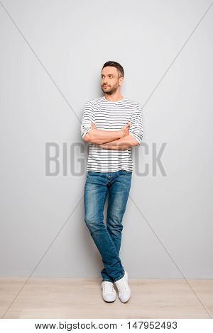 Portrait Of Stylish Man Standing Near The Wall With Crossed Hands
