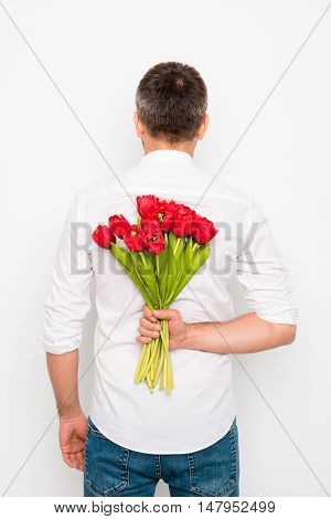 Back View Of Romantic Man Holding Bouquet Of Tulips