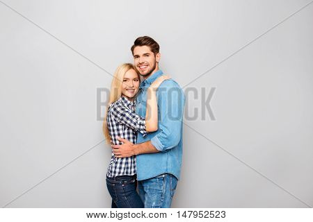Young Couple In Love Embracing Isolated On Gray Background