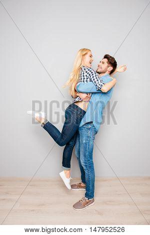 Portrait Of Romantic Couple. Happy Guy Carrying His Girlfriend
