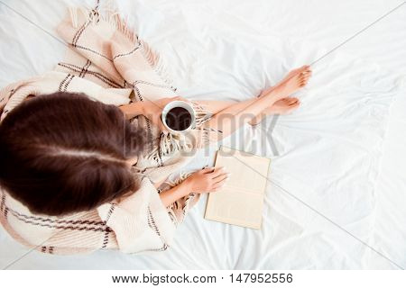 Top View Of Young Woman Reading Book And Basking With Plaid And Coffee