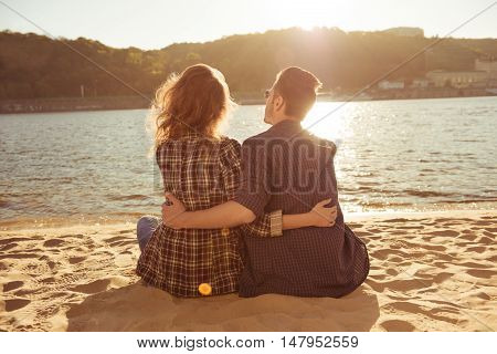 Back View Of Romantic Couple Sitting On The Beach And Huging