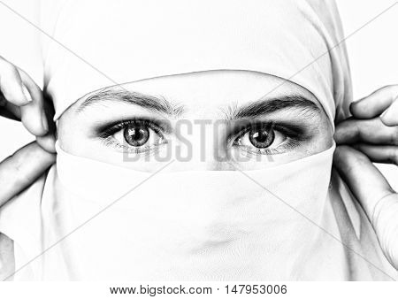 close-up beautiful mysterious eyes eastern woman wearing a hijab, black and white.