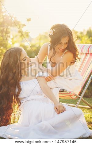 Two sisters. Girls in white dresses in the garden. Family time. Human relationships. Setting sun. Fun.