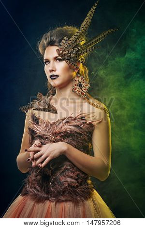 Girl harpy. Creative makeup for Halloween. The concept of magic creature. Curious.