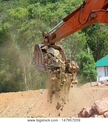 rusty orange bulldozer shovel arm, just starting to release a load of rocks, forest trees and white building in the background, Songkhla, Thailand