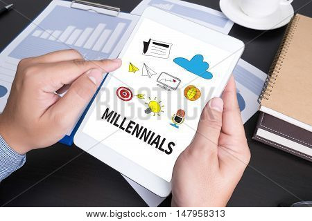 MILLENNIALS Modern people doing business graphs and charts being demonstrated on the screen of a touch-padblank screen copy space poster