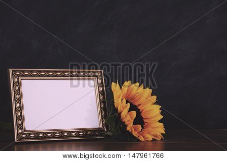 Picture Frame And Sunflower Against A Dirty Blackboard Background Vintage Retro Filter.