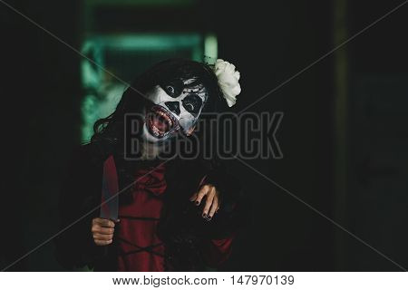 Scary girl with sharp knife shouting at camera