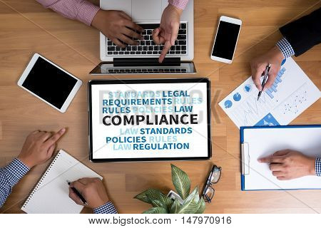 COMPLIANCE Business team hands at work with financial reports and a laptop top view poster