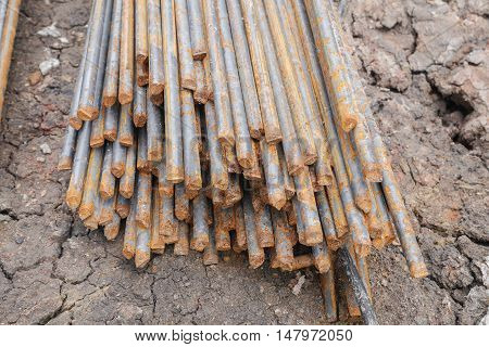Stack of rusty round steel bar - iron metal rail lines material for industry construction.