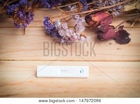 pregnancy test and dried flowers on wooden background. process dark tone