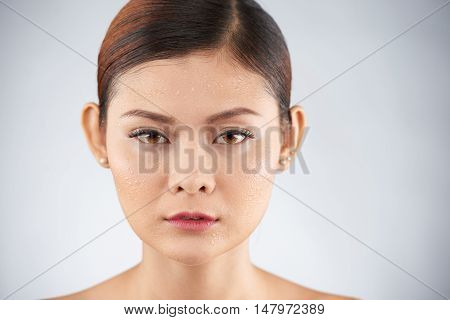 Face of unsmiling Vietnamese young woman with drops of water of her skin
