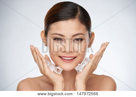 Smiling woman applying ice cube treatment on face