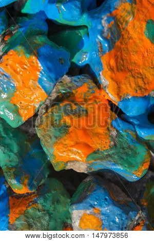 paint painted stones closeup. Painted in orange, blue, green color