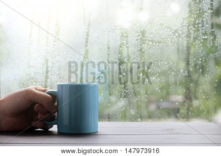 hand with a blue cup on a wooden table against the window with drops after rain / breath of autumn mood