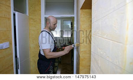 House Painter Paints Wall With Brush. Home Renovation.  Man Applying Paint With A Brush Onto Textured Wall .