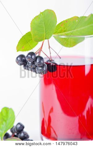 Glass of aronia juice with berries in the light background