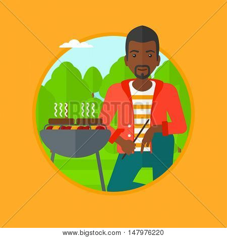 An african-american man sitting next to barbecue grill in the park. Man cooking meat on barbecue grill. Man having barbecue party. Vector flat design illustration in the circle isolated on background.