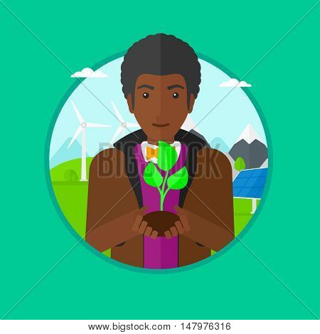 An african-american young man holding in hands green small plant in soil on a background with solar pannels and wind turbins. Vector flat design illustration in the circle isolated on background.