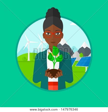 An african-american young woman holding in hands green small plant in soil on a background with solar pannels and wind turbins. Vector flat design illustration in the circle isolated on background.
