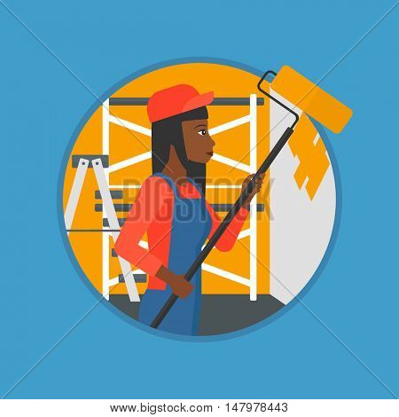 An african-american painter in overalls with a paint roller in hands. Painter painting walls with a paint roller in an apartment. Vector flat design illustration in the circle isolated on background.